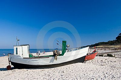 Two small fishing boats on a sandy beach.