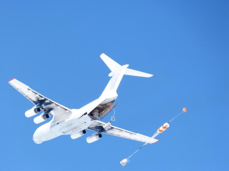 El cielo diáfano de la Antártida, y el avión que arroja la carga en Belgrano II.