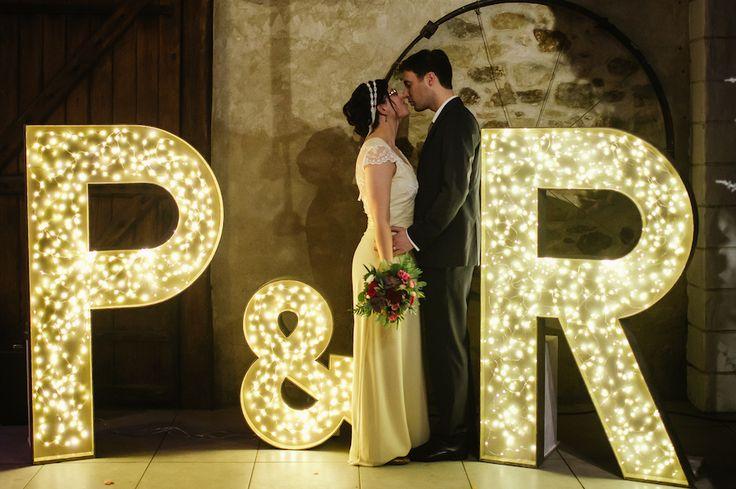 Photos de couple devant des grosses initiales lumineuses