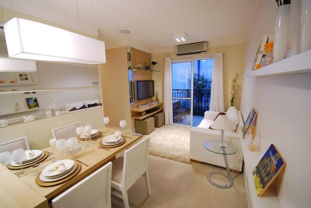 Sala pequena, porém charmosa! Para criar um ambiente aconchegante não é necessário muito espaço. A #decoração clean branca amplia a sala e os móveis planejados harmonizam o ambiente.   Puffs sob o rack