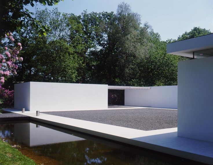 The arrival courtyard with the windowless side wall to the top lit annexe and red cedar canopy to the carport.Stainless steel bollards make the crossing point from the bridge to the square gravel courtyard with its limestone perimeter.