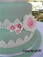 De zijkant van de taart met grote rozen en een kanten randje.