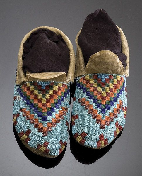 "Sioux Beaded Hide Moccasins - Cowan's Auctions  Sioux Beaded Hide Moccasins, 2005, American Indian Arts / Sep 7 - 8 thread and sinew-sewn with motif of an eye-catching design of stepped blocks in colors of red, orange, light blue, greasy yellow, white striped red, and green beads, length 9.5"".  Provenance:   Ex Ben Thompson Collection  Condition:   Cuffs and tongue was edged with silk(?) ribbon - which is now mostly missing. Sold: $431.25"