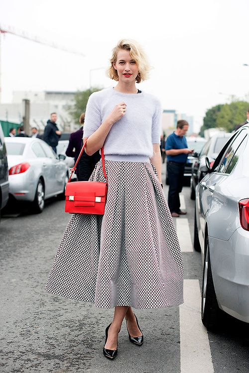 Shop this look on Lookastic:  http://lookastic.com/women/looks/light-blue-cropped-sweater-and-white-and-black-full-skirt-and-black-heels-and-red-satchel-bag/2400  — Light Blue Cropped Sweater  — White and Black Geometric Full Skirt  — Black Leather Pumps  — Red Leather Satchel Bag