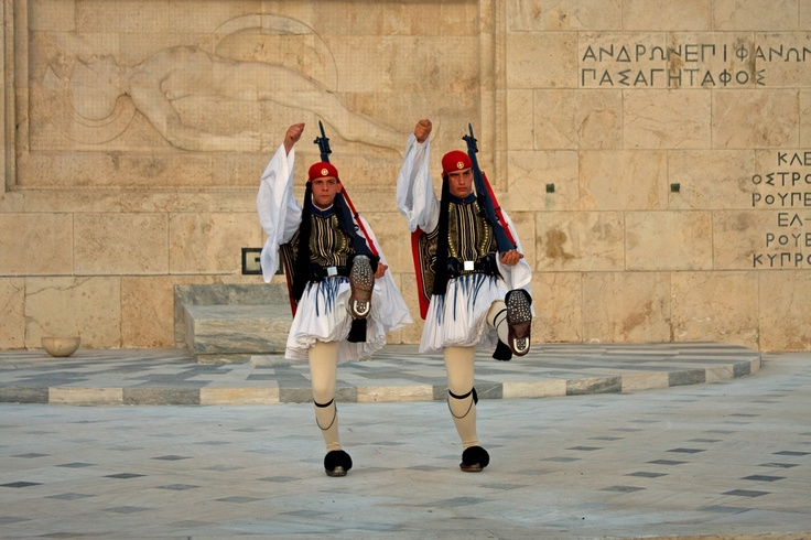 The Evzones, or Evzoni, was a name used for several historical figures of the Greek Army who used to fight on the mountains. Today, it refers to the members of the Presidential Guard, an elite ceremonial unit that guards the Greek Tomb of the Unknown Soldier, the Hellenic Parliament and the Presidential Mansion. The Evzones are also known, as Tsoliades. The unit is famous around the world for its unique traditional uniform.  Here the guards are performing the ceremonial guard change.