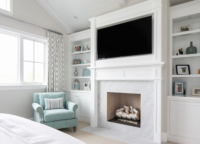 The Master Bedroom Features A Classic White Marble Fireplace Surround With White Bookshelves Cabinetry On Both