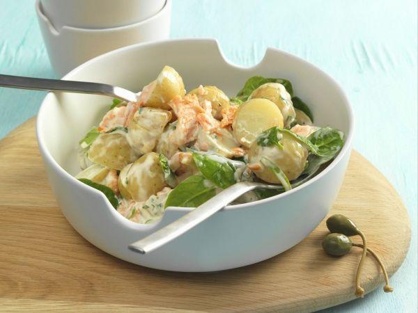 Aardappelslaatje met gerookte zalm, spinazieblaadjes en dressing van zure room