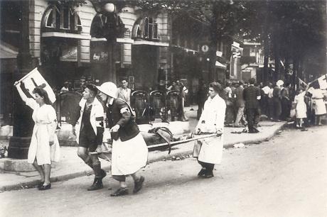 Des secouristes transportent un blessé sur un brancard - © L.A.P.I. - CRF  1949 : La Croix-Rouge française récupère les missions de secours à la population civile. (Convention de Genève) 1952 : pendant la guerre froide, la Croix-Rouge française est intégrée au plan ORSEC.