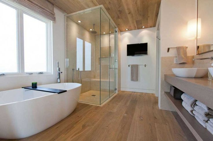 Small Modern Bathroom Design Ideas with oval bathtub and glass shower enclosure on wood laminate flooring