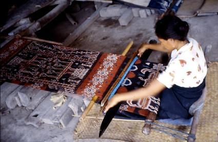 Sumbanese woman weaving a warp ikat hinggi with a traditional back strap loom. http://www.njcharters.com/nj_charters_blog/uploaded_images/Indonesia-Sumba-Island-villager-weaving-Ikat-Textile-707294.jpg