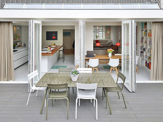 Sfeervolle stadstuin met verhoogd terras. Dankzij de  openslaande deuren naar de tuin is er een optimale verbinding tussen de keuken de tuin. Ontwerp van Bloem en Lemstra Architecten