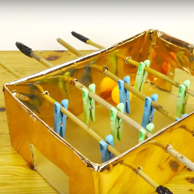 Heb je nog ergens een oude doos rondslingeren? Maak er een mini-tafelvoetbal van en organiseer een buurttornooi! Dit heb je nodig: een kartonnen doos stevige plakband (bijvoorbeeld duct tape) scherp mes optioneel: verf, inpakpapier, andere versieringen stift of pen dunne, maar stevige stokken (bijvoorbeeld bamboe) wasknijpers pingpongballetje of ander licht, klein balletje Als je doos … Continued