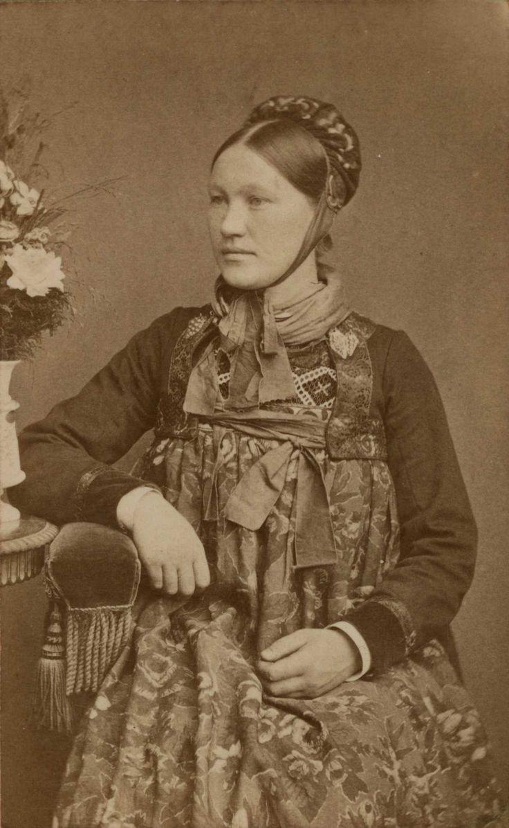 Kvinnedrakt fra Nes,  Hallingdal, Buskerud. Portrett av av jente/kvinne sittende ved bord i fotoatelier.