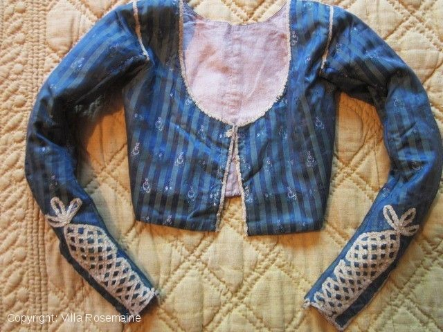 """Early Regency French """"Merveilleuses"""" caraco - late 18c - Circa 1795/1800 Directoire jacket or caraco for young women inspired by the """"à la cavalière"""" fashion from England at the late 18th c. Silk pekin taffeta green and blue brocaded with small moons n bouquets, Bonaparte's Egyptian Campaign. Fully piped with pale yellow braid. Very long sleeves oversized and widely covering hands. six buttons each hand. waist 58 cm, 31 cm shoulders, sleeves 55 cm, height of back 26 cm, front height  16 cm."""