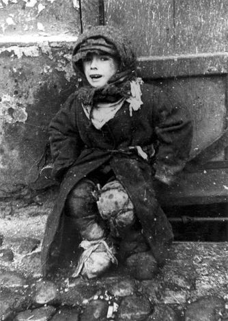 A boy dressed in rags sitting on a street in the ghetto. Warsaw, Poland