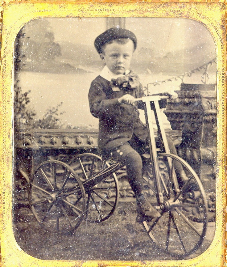 A boy on a wooden tricycle
