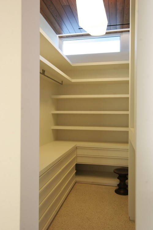 A fairly efficient walk-in closet layout. Ample room @ top for infrequently used large items Lowest shelf could serve as a bench with drawers or cabinets concealed within.