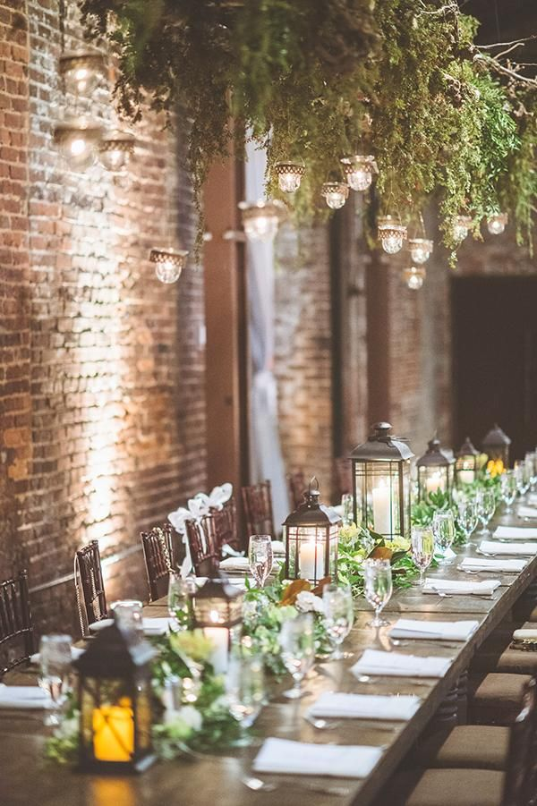 Hanging installation with greenery and votives in an urban brick venue.