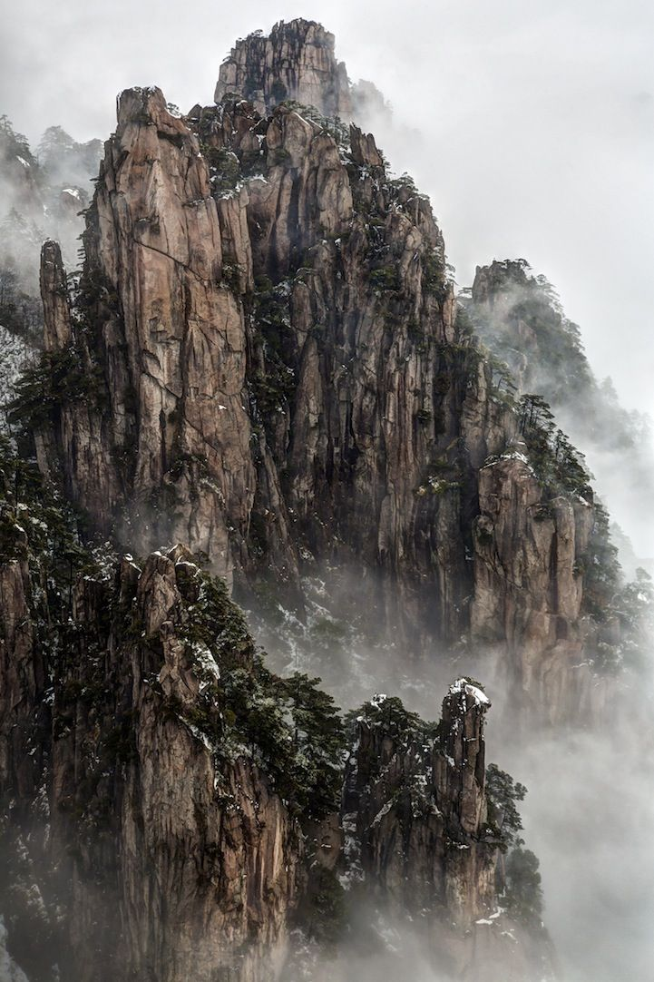 "Photographer Chaluntorn Preeyasombat calls this photo Clearing Storm. ""Huangshan Mountain, Anhui, China. Taken from the Beginning-to-Believe Peak after morning snowfall. The lingering fog made the scene look like Chinese painting."""