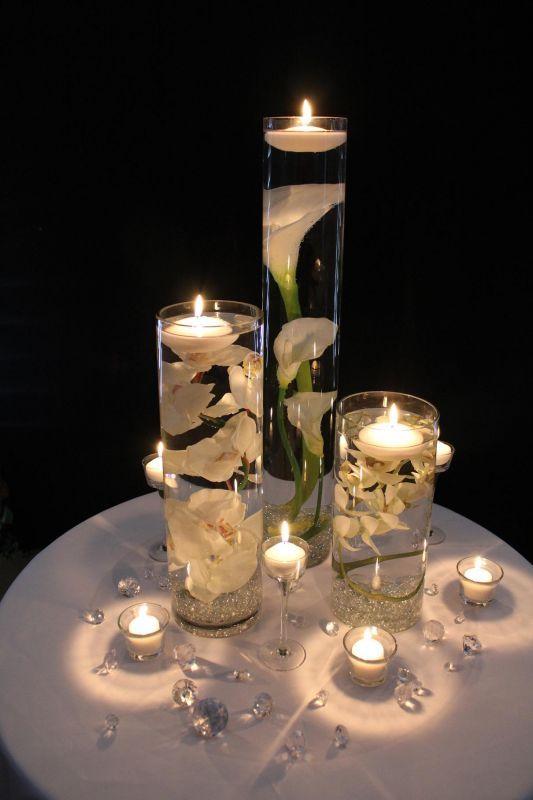Centros de mesa con velas flotantes y cartuchos sumergidos.