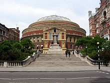 The Royal Albert Hall was built with profits from the Great Exhibition, + commemorated the death of Prince Albert in 1861. Queen Victoria laid the foundation stone in 1867, + opened it 4 yrs later on 29.3.1871. Designed by Captain Francis Fowke & Henry Darracott.  The most famous event held is the Sir Henry Wood Promenade Concerts – or The Proms. Originally held in the Queen's Hall, South Bank, until bombed in 1941 by the Germans. It transferred to the Royal Albert Hall + rose in popularity.