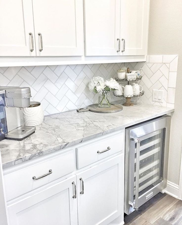 Wine fridge, white cabinets, grey counters