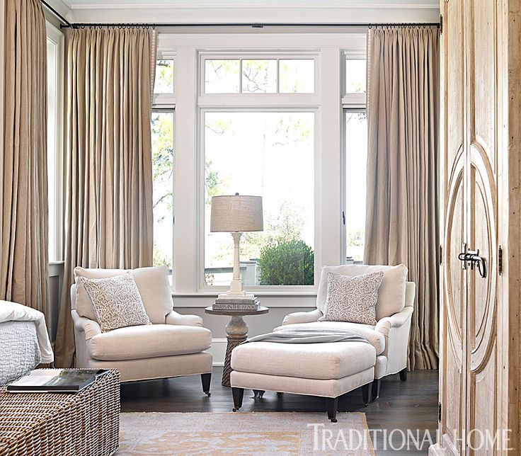 cozy conversation nook in the bedroom is framed by rich linen drapes
