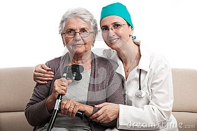 Portrait of a nurse or female doctor visiting an and old disabled woman. Happy people portrait. Isolated on white.