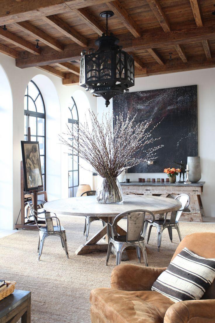 Hauts plafonds bois, sol minéral clair, ouvertures baies arc plein cintre. Déco campagne.