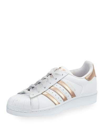 """adidas leather low-top sneaker with metallic striped sides. 1"""" flat heel. Textured round toe. Lace-up front. Logo-embossed heel counter. Padded footbed. Rubber outsole. """"Superstar"""" is imported."""