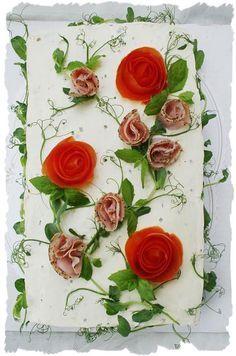 """Voileipäkakun päälle voi valmistaa kauniin ruusun tomaatista. Unelmakakut-kirjassani on kerrottu miten tämä tapahtuu, löydät sieltä paljon myös muita vinkkejä koristeluun ja erityisesti kakkuihin. Pese tomaatit ensin hyvin ja kuori kuorimaveitsellä tomaatin kuorta samalla kiertäen, kunnes kuori on kierretty kokonaan tomaatista. Rullaa pitkä kuoriosa """"rullalle"""", jolloin siitä tulee ruusun näköinen. 1, 5 pkt Oululaisen Reilu- vehnäpaahtoa kakkuun tuli myös 1 leveä kerros ruisvuokaleipää…"""