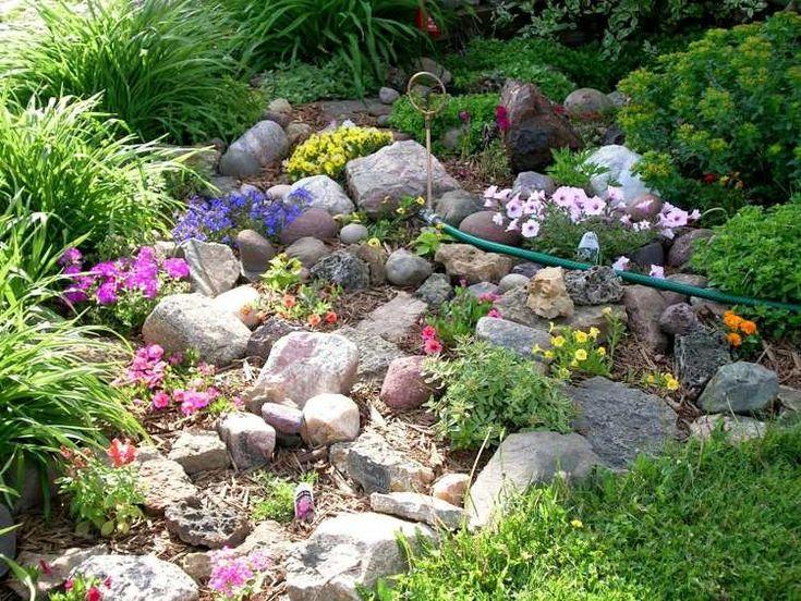 jardin de rocaille avec des pierres naturelles, fleurs multicolores et graminées d'ornement