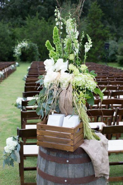 Ceremony programs in a wooden crate at the aisle entrance on a wooden barrel | Classic Southern Wedding With A Vintage Twist At Tennessee's Spring Creek Ranch | Photograph by Christen Jones Photography  http://storyboardwedding.com/classic-southern-wedding-tennessee-spring-creek-ranch/