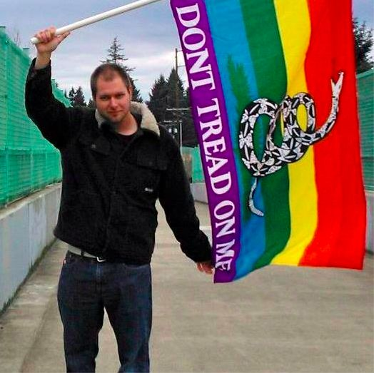 James Holcomb, a 29-year-old libertarian, stands with a rainbow Gadsden flag. Holcomb adamantly supports  both gay rights and gun rights. (Photo courtesy of James Holcomb)