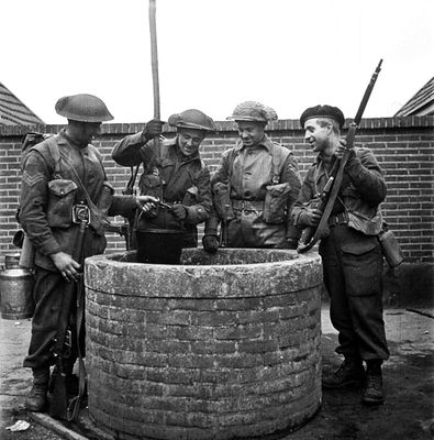 Infantrymen of Les Fusiliers Mont-Royal drawing water from a well near Laren, Netherlands, 6 April 1945. (L-R): Sergeants Phillip Jean and Roger St. Jean, Corporal Dejenaes Mendoza, and Private Maurice Boisvert.