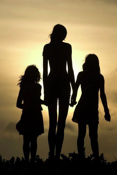 A photograph of Elisany Silva, the tallest teen girl in the world, and her sisters. Photography by Paulo Santos via Reuters. #elisany #silva #tall #girls #silhouettes #sisters #sky #light #height #paulo_santos