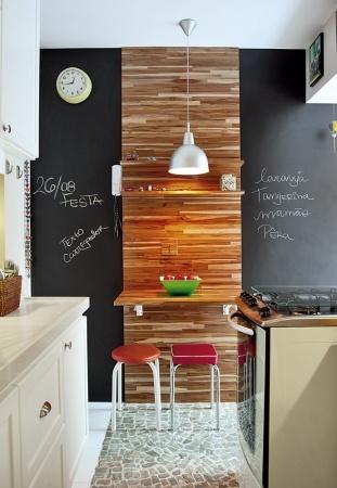 Recado: Em vez de usar tinta de lousa, Fernanda Nobre aplicou a lousa pronta na parede, que, segundo ela, dá menos trabalho para limpar. Ao centro, um painel de teca com mesinha acoplada. Os banquinhos são da Tok&Stok