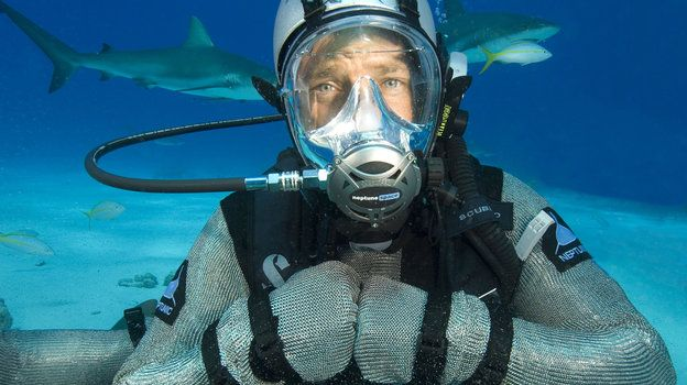 "Mike Rowe scubas in protective underwater gear as he hosts an episode of Discovery Channel's ""Shark Week."" Critics say sensationalized wildlife documentaries, like some of those broadcast during Shark Week, do more harm than good."