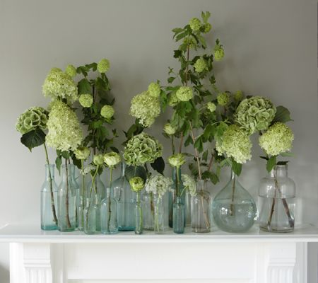 Key to making this work - flowers are the same color in glass vases of varying shapes and sizes