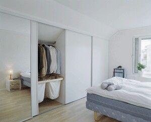 Garderob under snedtak med skjutdörrar och spegel