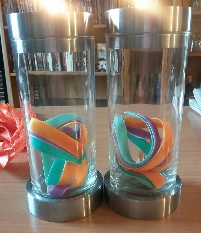 Candlesticks decorated with green, purple and orange ribbon.