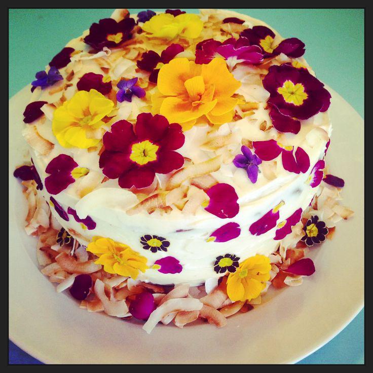 spring flowering primroses and primulas adorn this red velvet celebration cake - edible flowers from greensofdevon.com