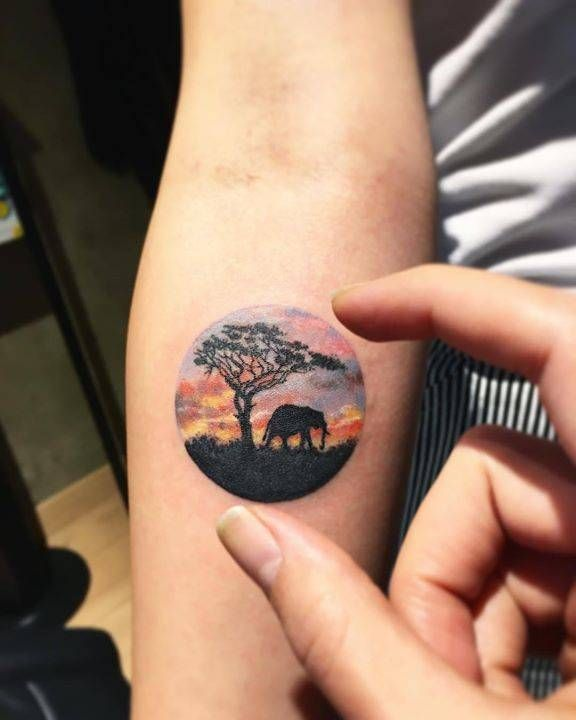 Safari landscape circle tattoo on the right inner forearm.