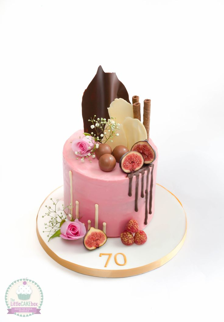 Drip cake with chocolate sails, fruit and flowers.