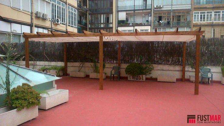 Pergola de madera de abeto laminado lasurado en color nogal.  Acabada con toldo corredero acrilico. Instalada en un sobreatico en Barcelona.  www.fustmar.com