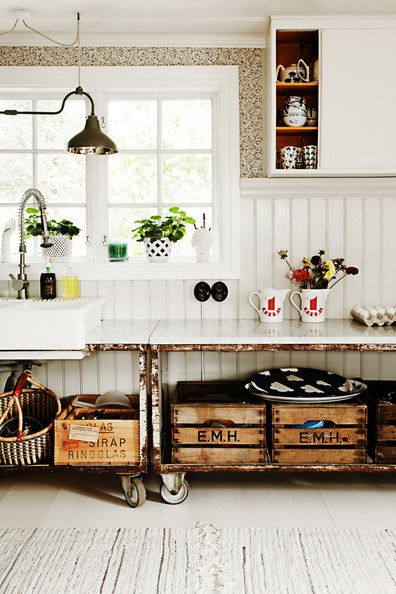 Painted wainscoting and vintage wooden crates add texture to a rustic Swedish kitchen.  by lonny.com