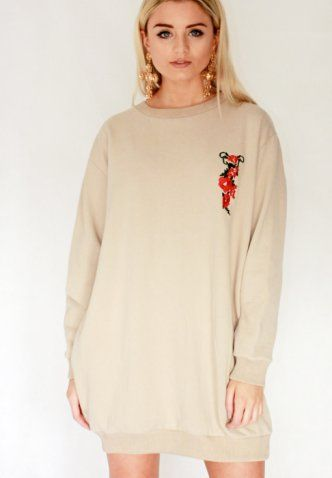 Work the romance trend with this embroidered rose appliqué sweater dress. Complete with pockets.