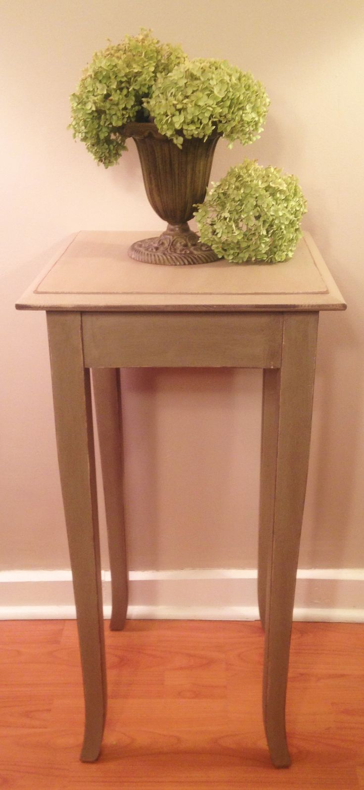 NEED A TOUCH OF COLOR...?   This tall accent table has just that.   Very attractive in a khaki green with distressed edges and finished in an Early American stain. Her slender but curvy legs give her a feminine touch!