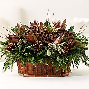 Rustic Natural Holiday Basket - Rustic and refined, this fall-inspired Christmas Basket is the perfect piece to welcome families home. Fresh holiday greens provide a verdant backdrop to burgandy protea, lotus pods and festive pinecones. Bark basket is included.