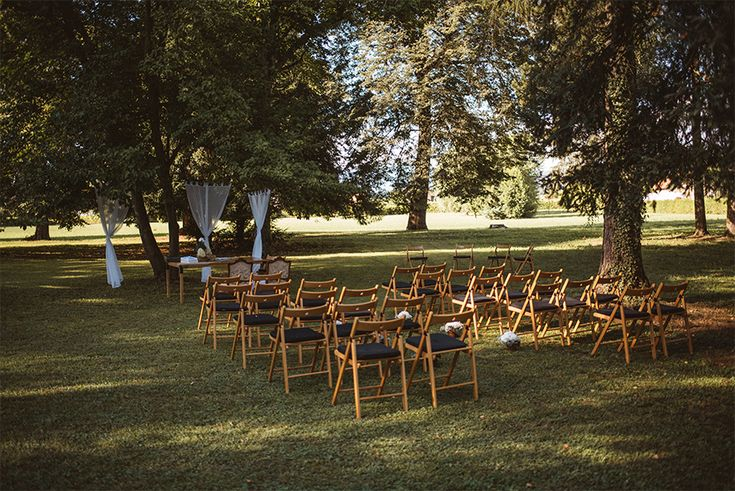 Wedding ceremony with modern chairs under the trees